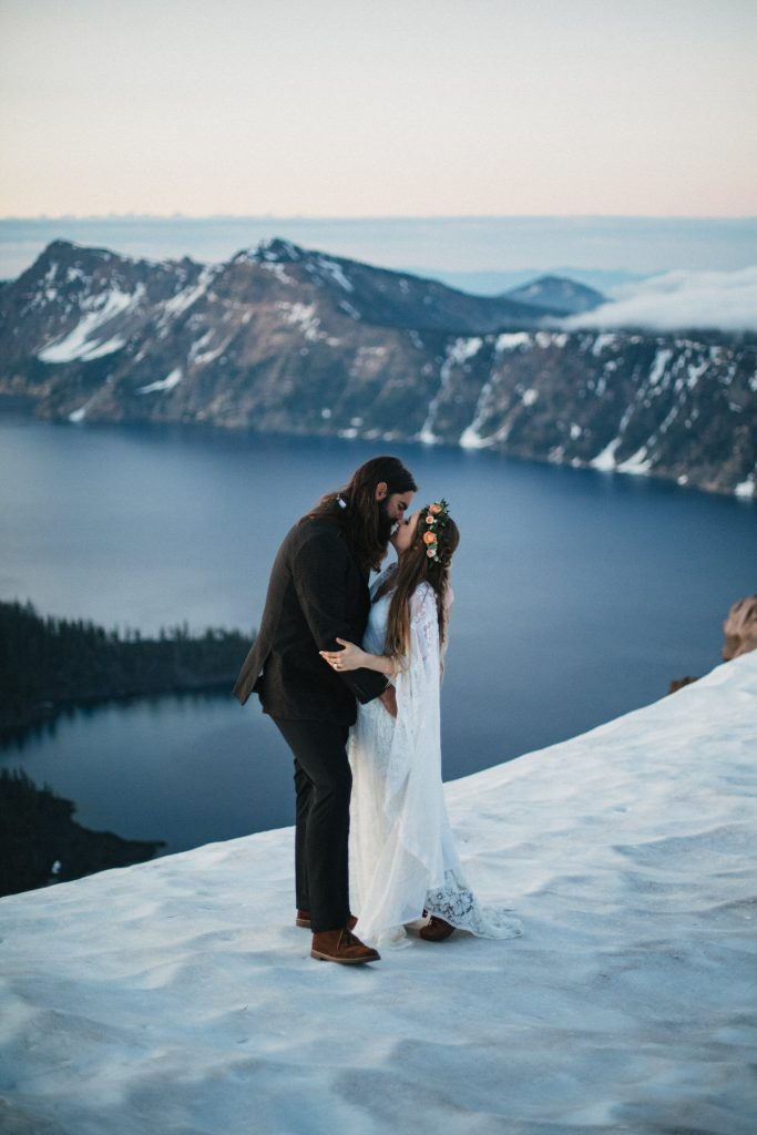 A wedding couple stands on the top of a snowy mountain and kisses each other.