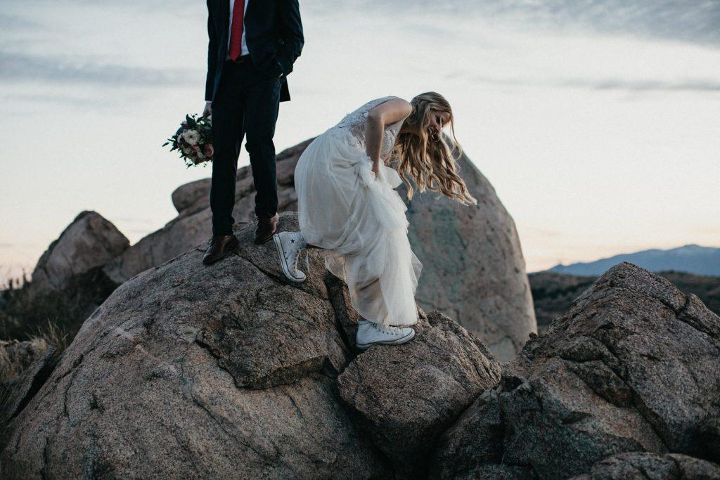 A bride tries to climb down a rock.