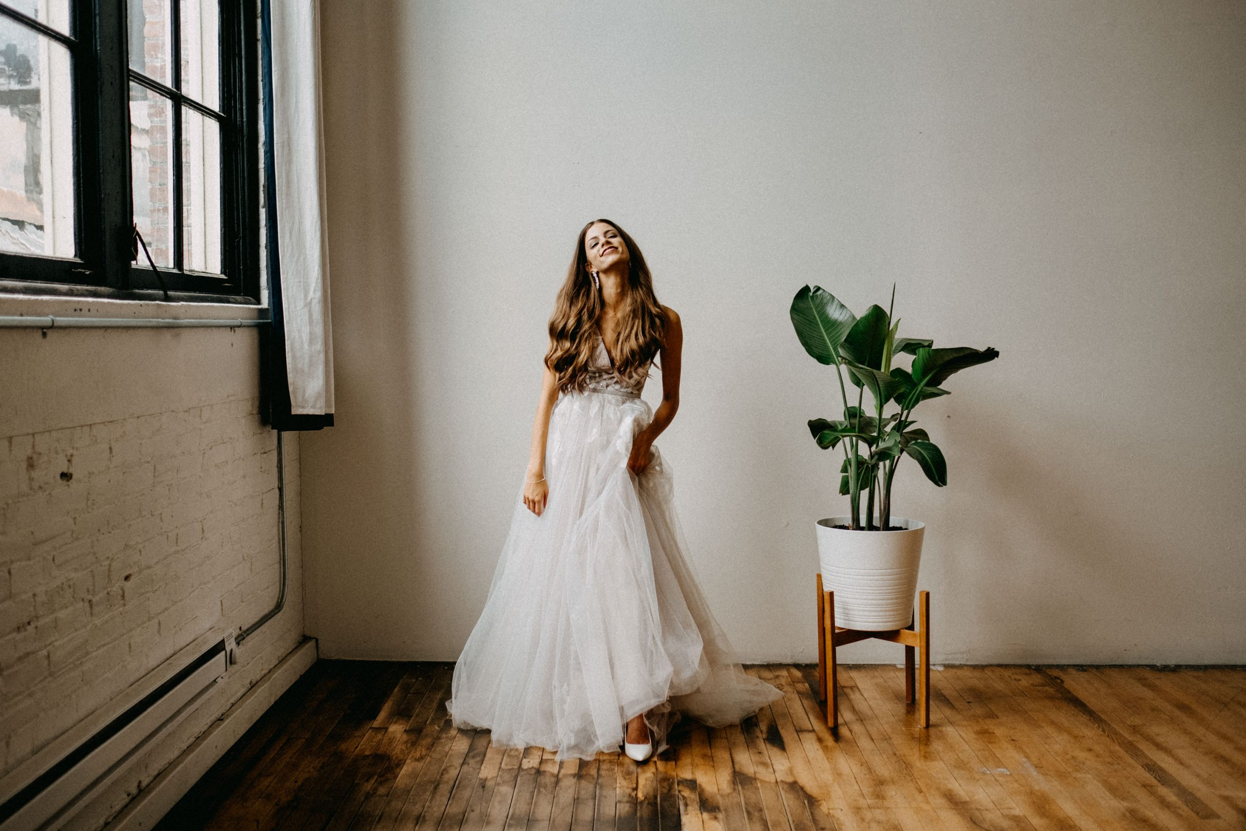 A portrait of a bride that stands between a window and a plant.