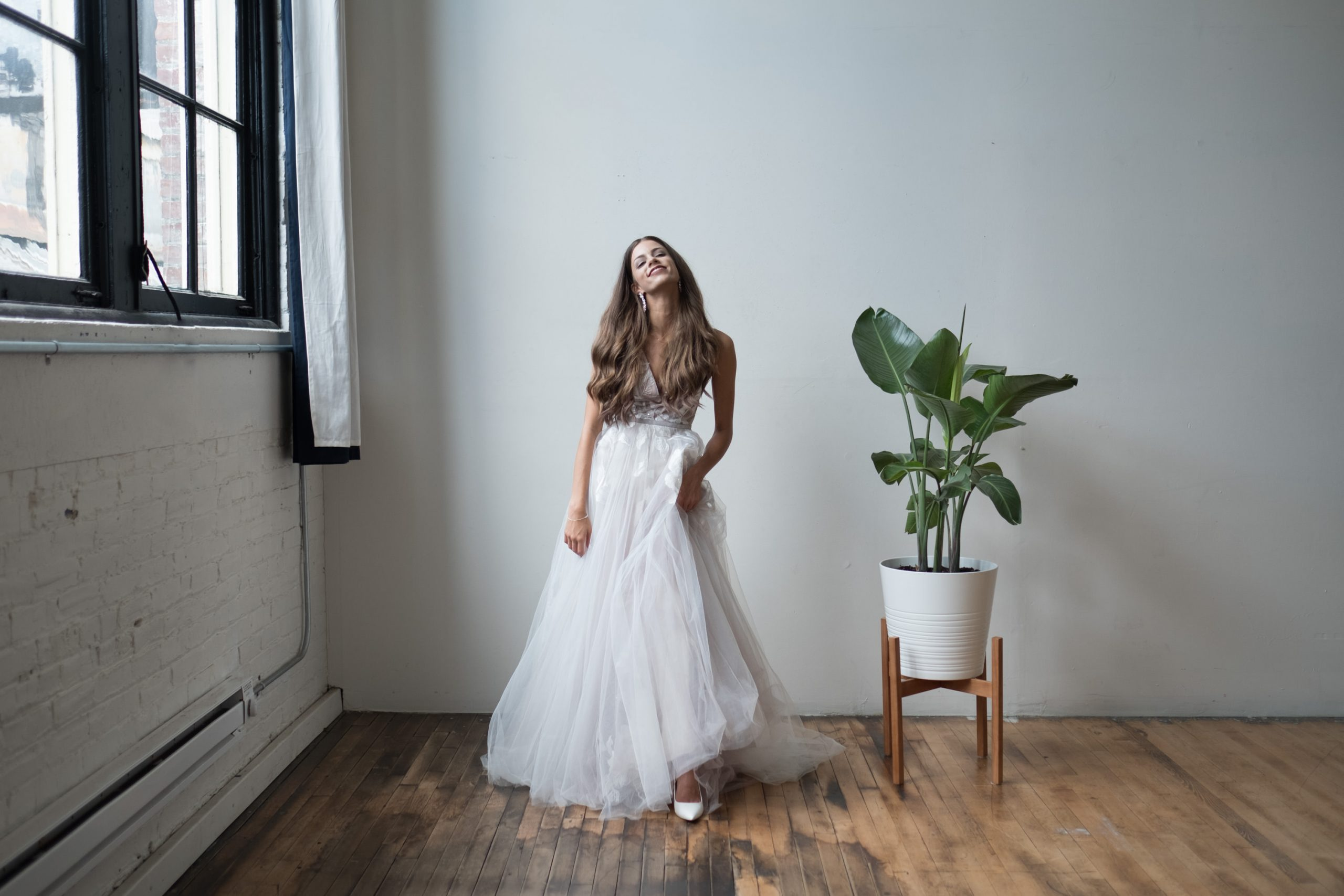 An unedited portrait of a bride that stands between a window and a plant.