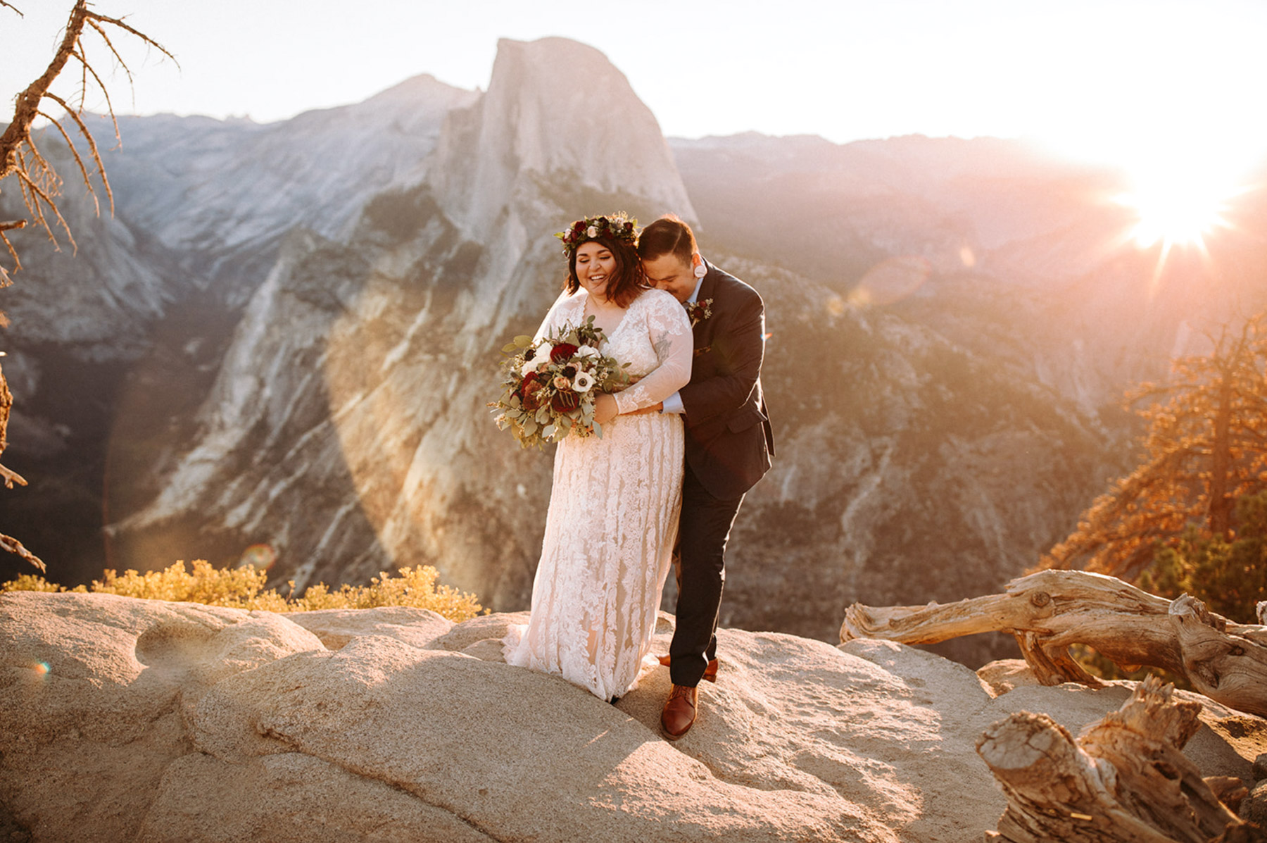 A wedding couple is embracing each other and they are standing on top of a mountain.