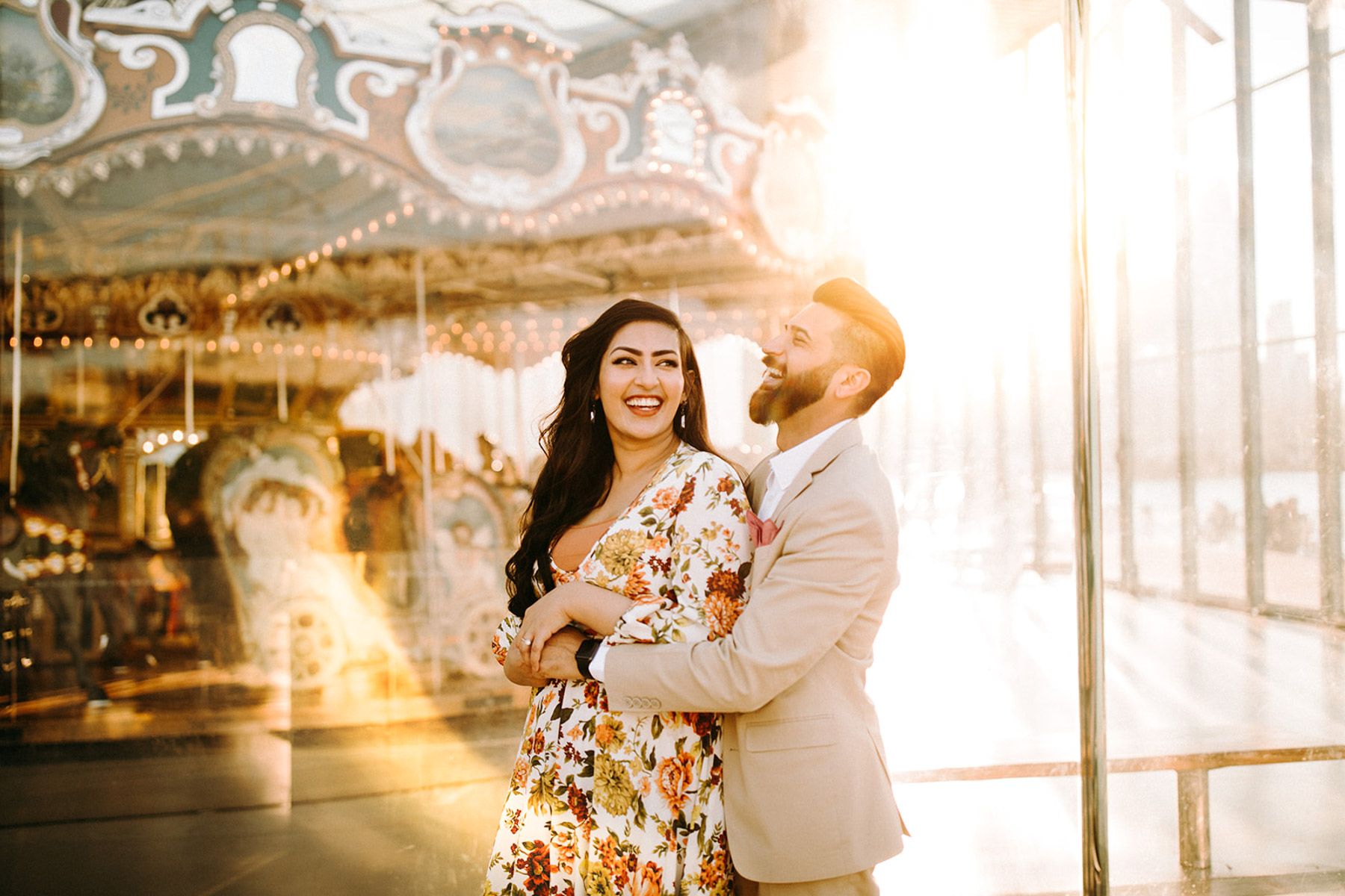 A couple is embracing each other and standing in front of a carousel.