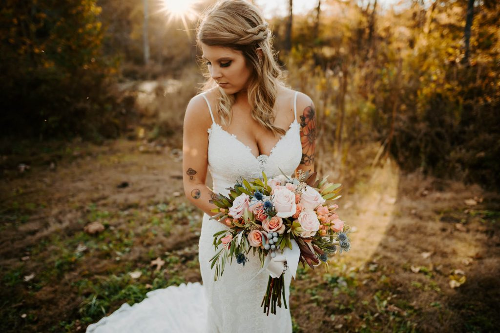 A bride is holding her flower bouquet and standing in the forest.