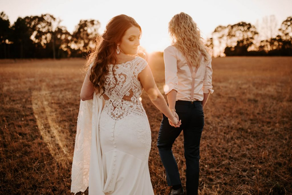 A wedding couple is holding hands and walking through a meadow.