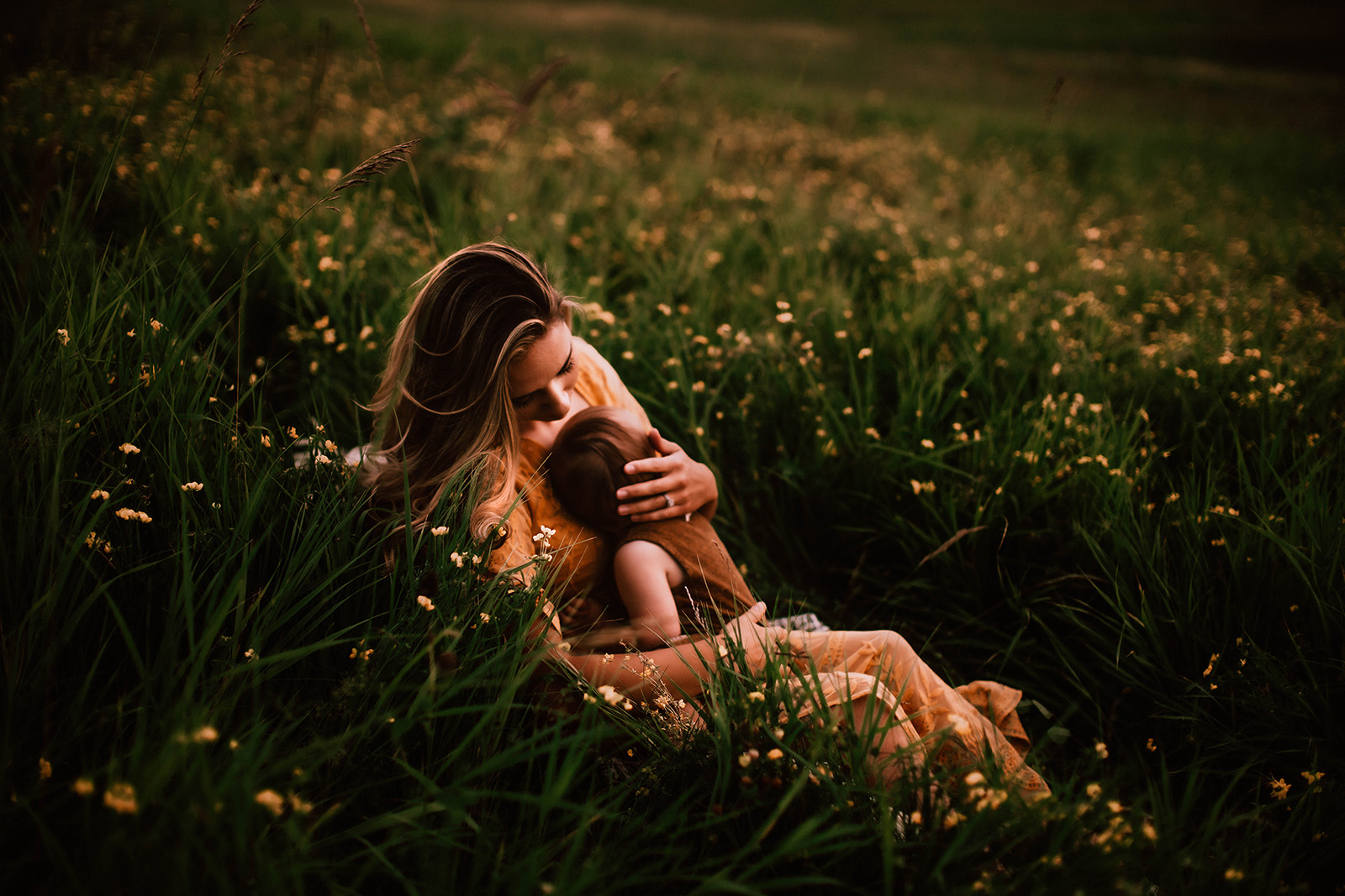 A woman is holding her child and they are sitting in a meadow.