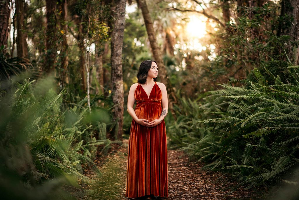 A pregnant woman is holding her belly and standing in the middle of the forest.