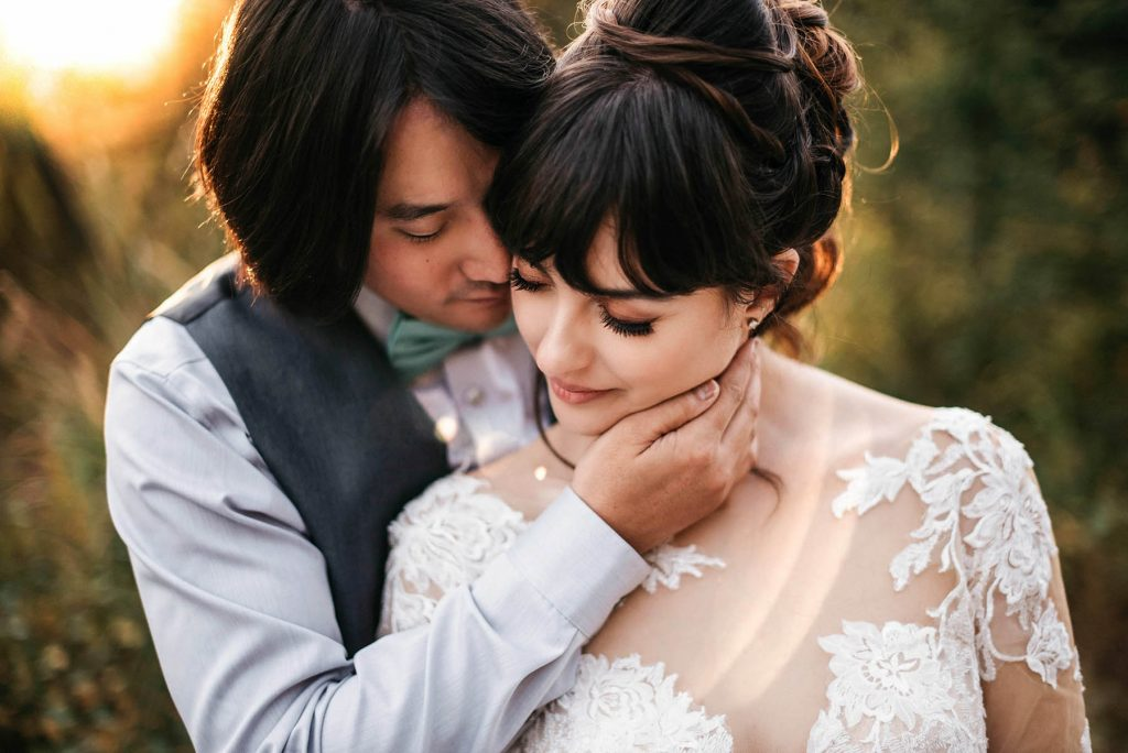 A closeup of a wedding couple holding each other.