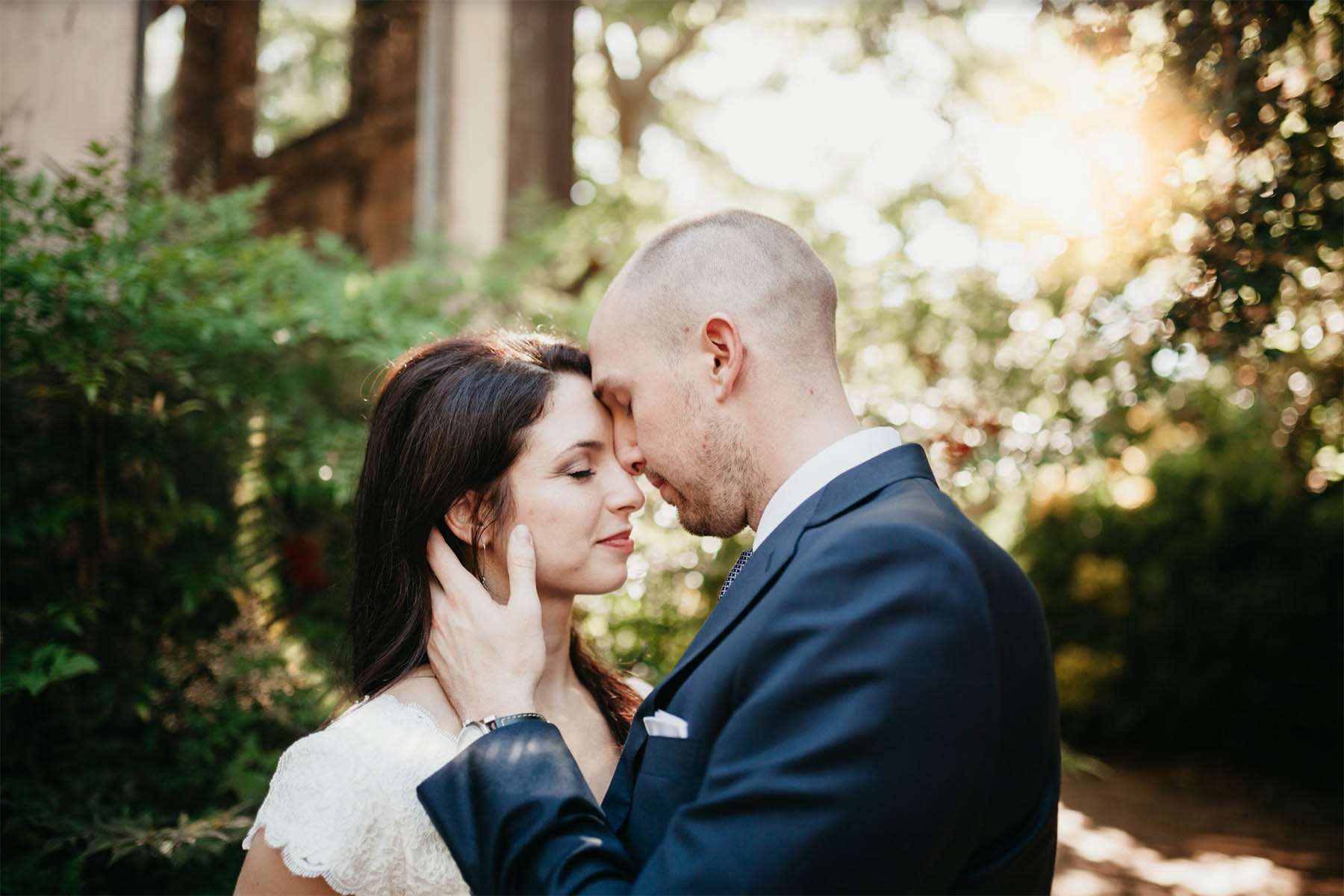 A couple is touching foreheads and they are standing in the forest.