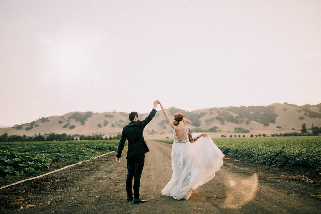 A wedding couple is holding up their hands and they are walking on a path next to fields.