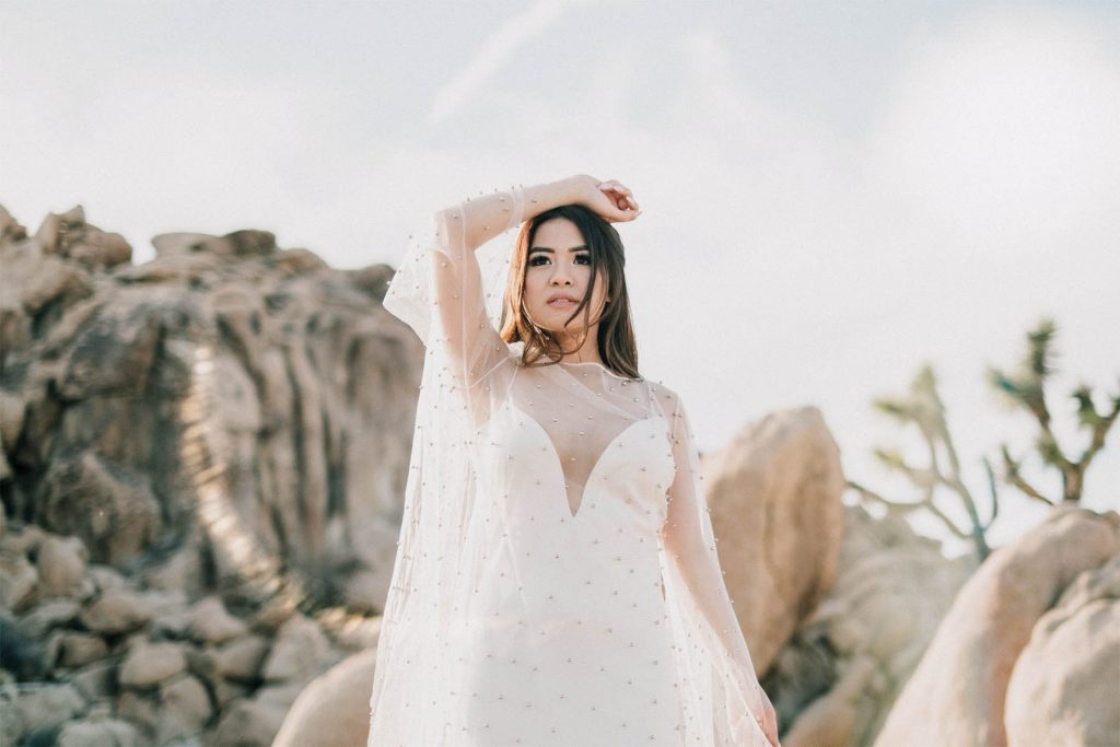 A woman is wearing a white dress and she is standing in front of rocks.