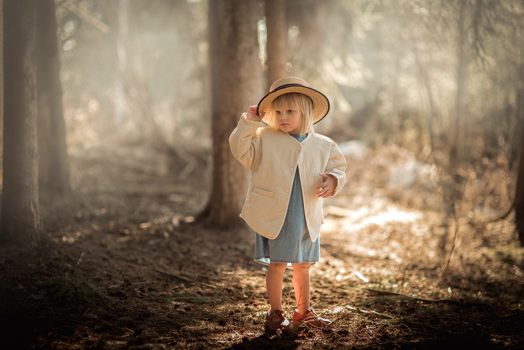 A little girl is standing in a forest.