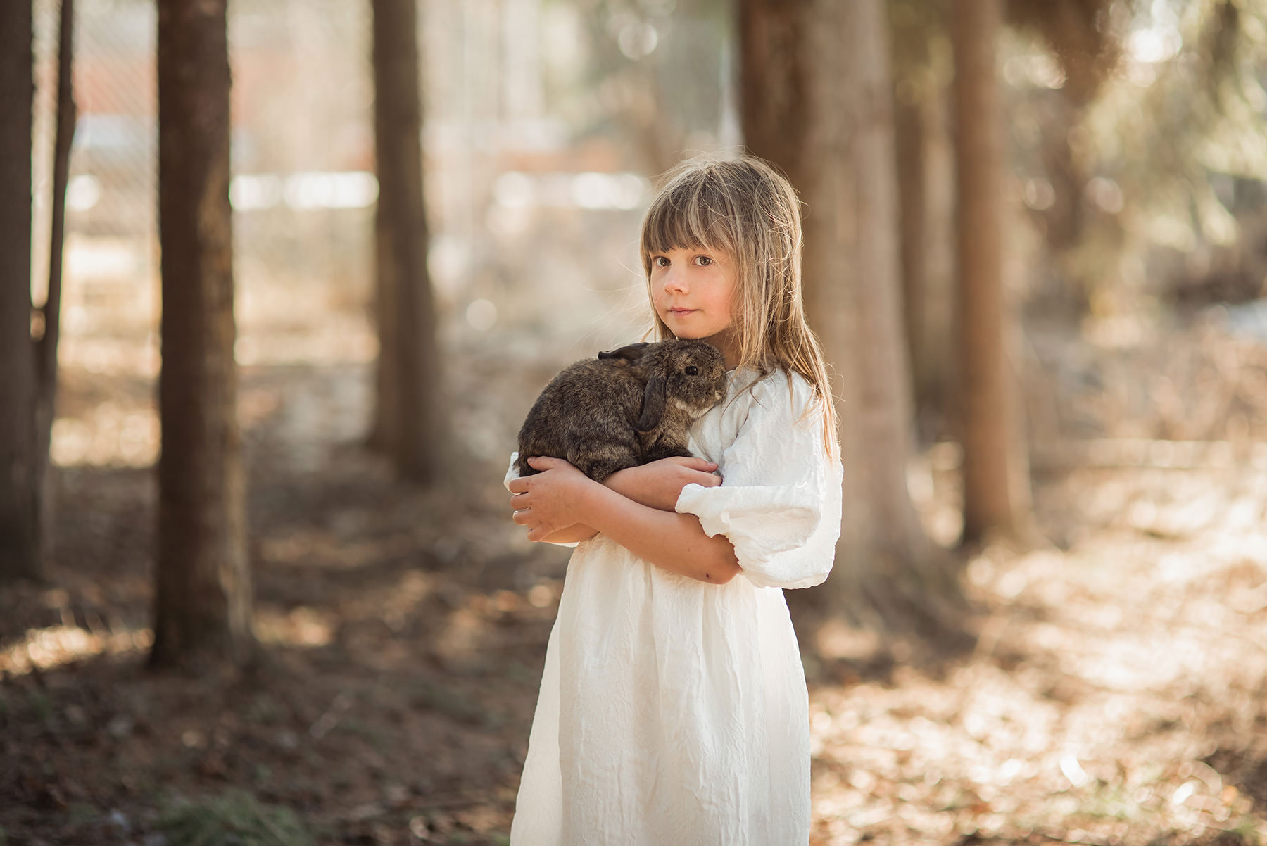 A girl is holding a cat and standing in the forest.