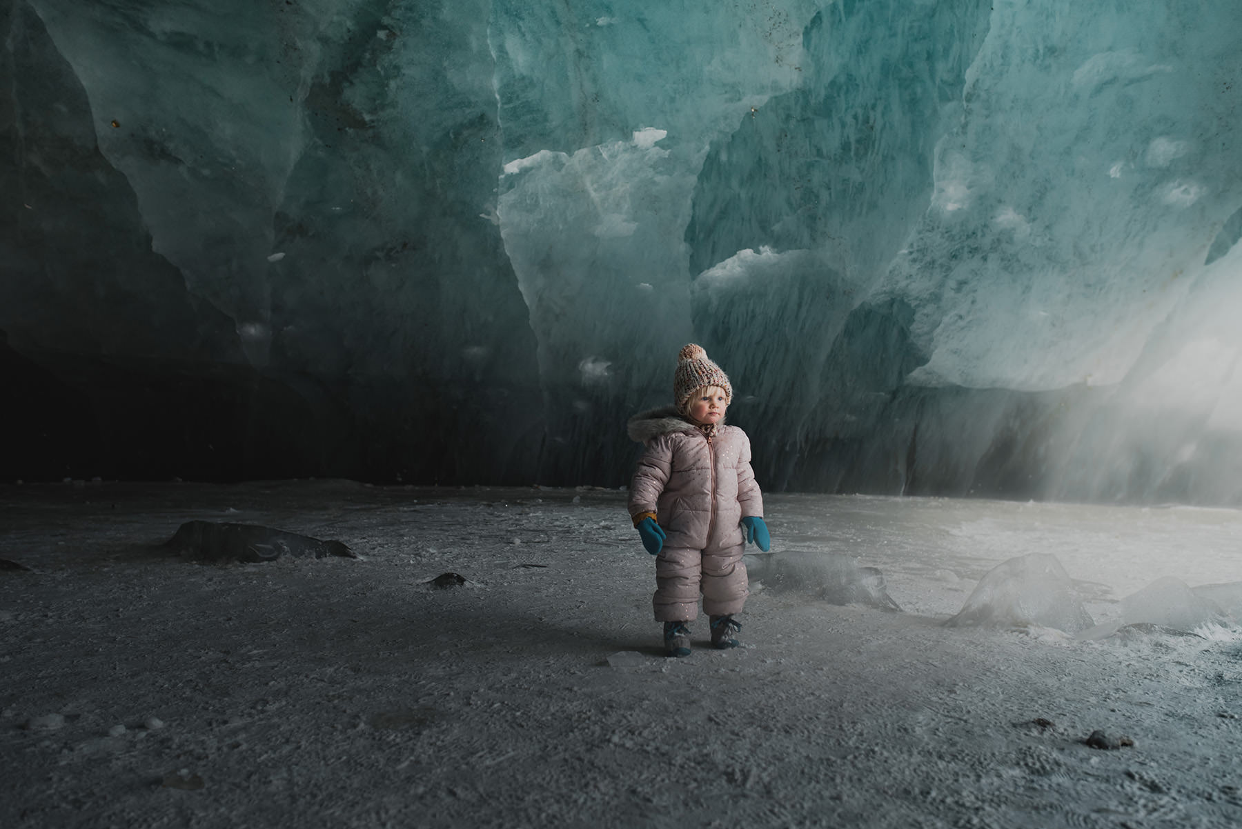A little child is standing in a cave.