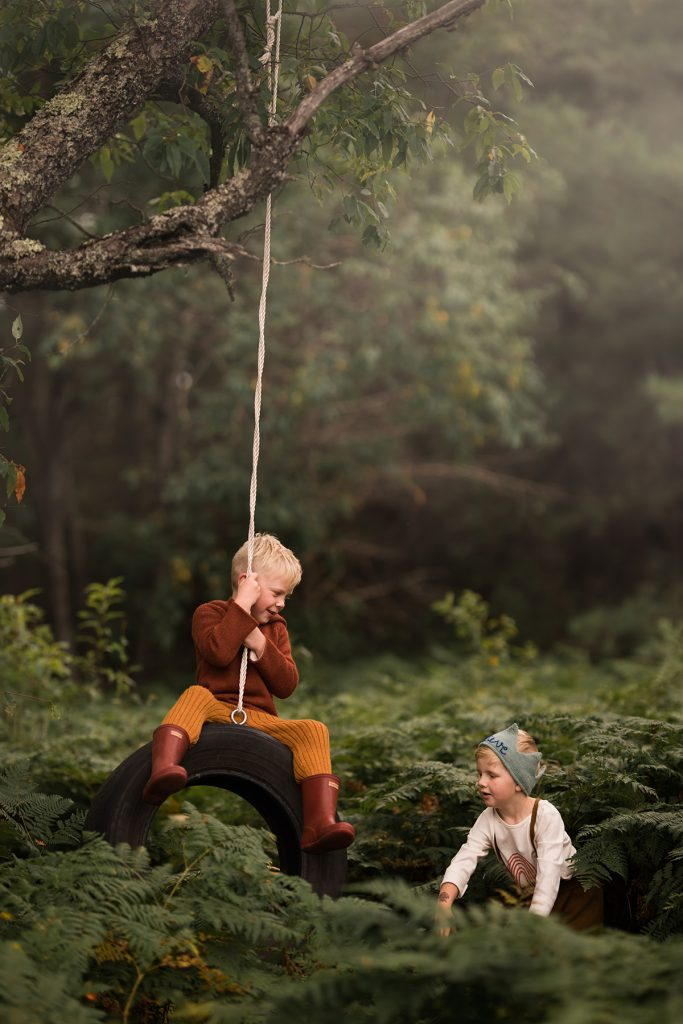 Two boys are playing in the forest and one of them is swinging on an old car tire.