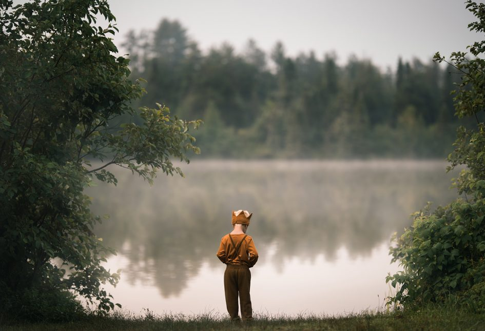 A child is standing in front of a lake.