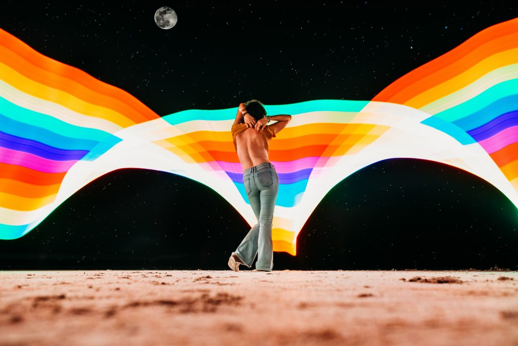 A woman is standing on a dry patch of land in the middle of the night and the Celestial Preset adds a rainbow to the background.