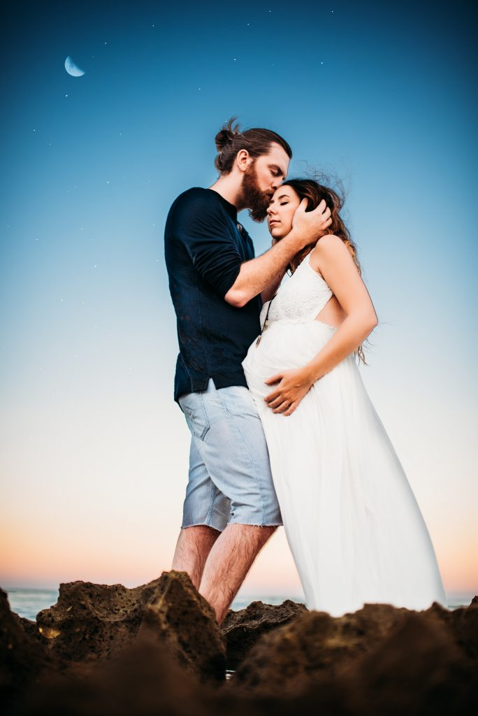 A man is kissing his pregnant woman on the forehead.