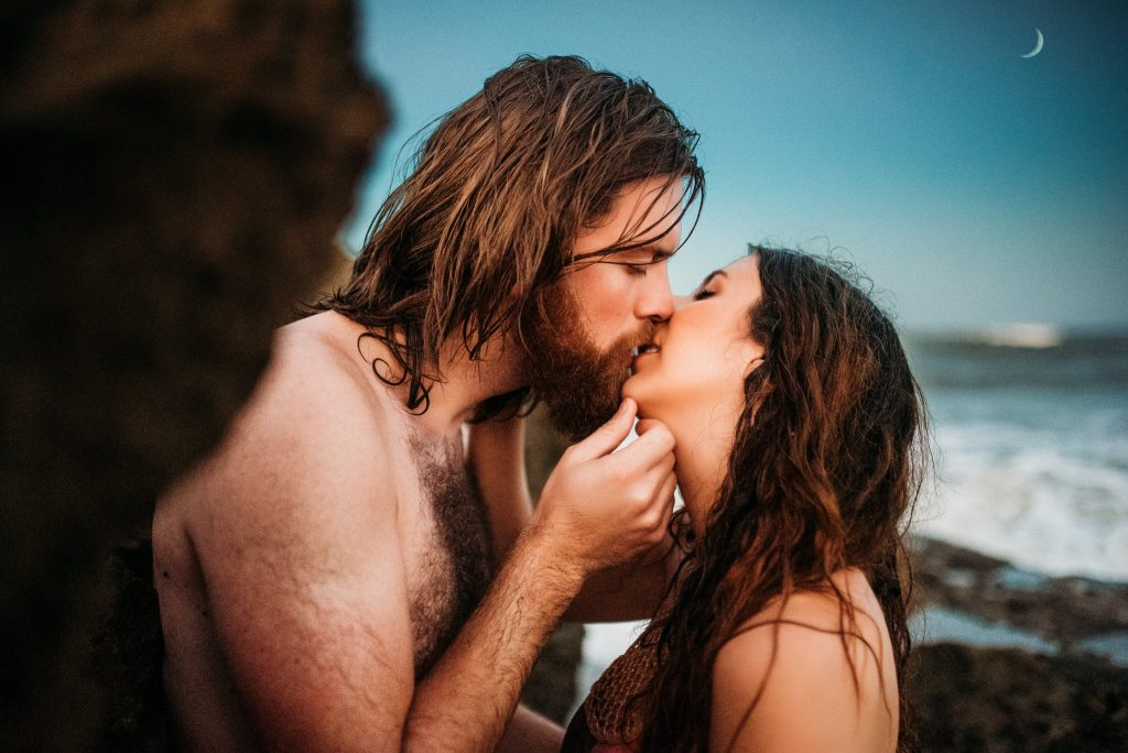 A couple is kissing each other passionately and they are standing at the beach.