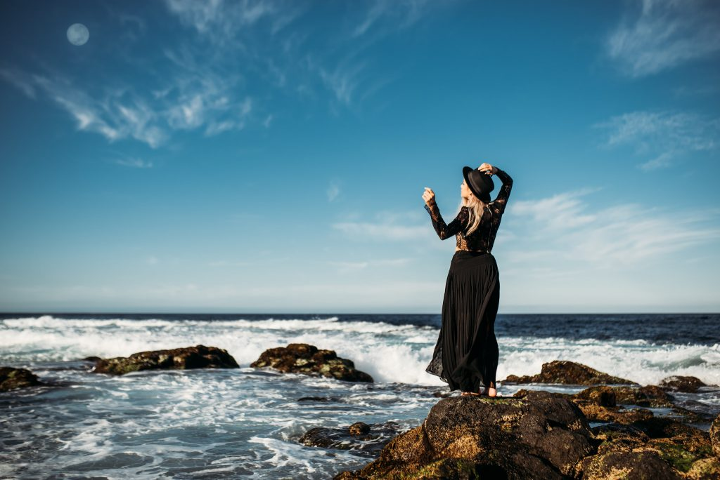 A woman is standing on a rock in the ocean.