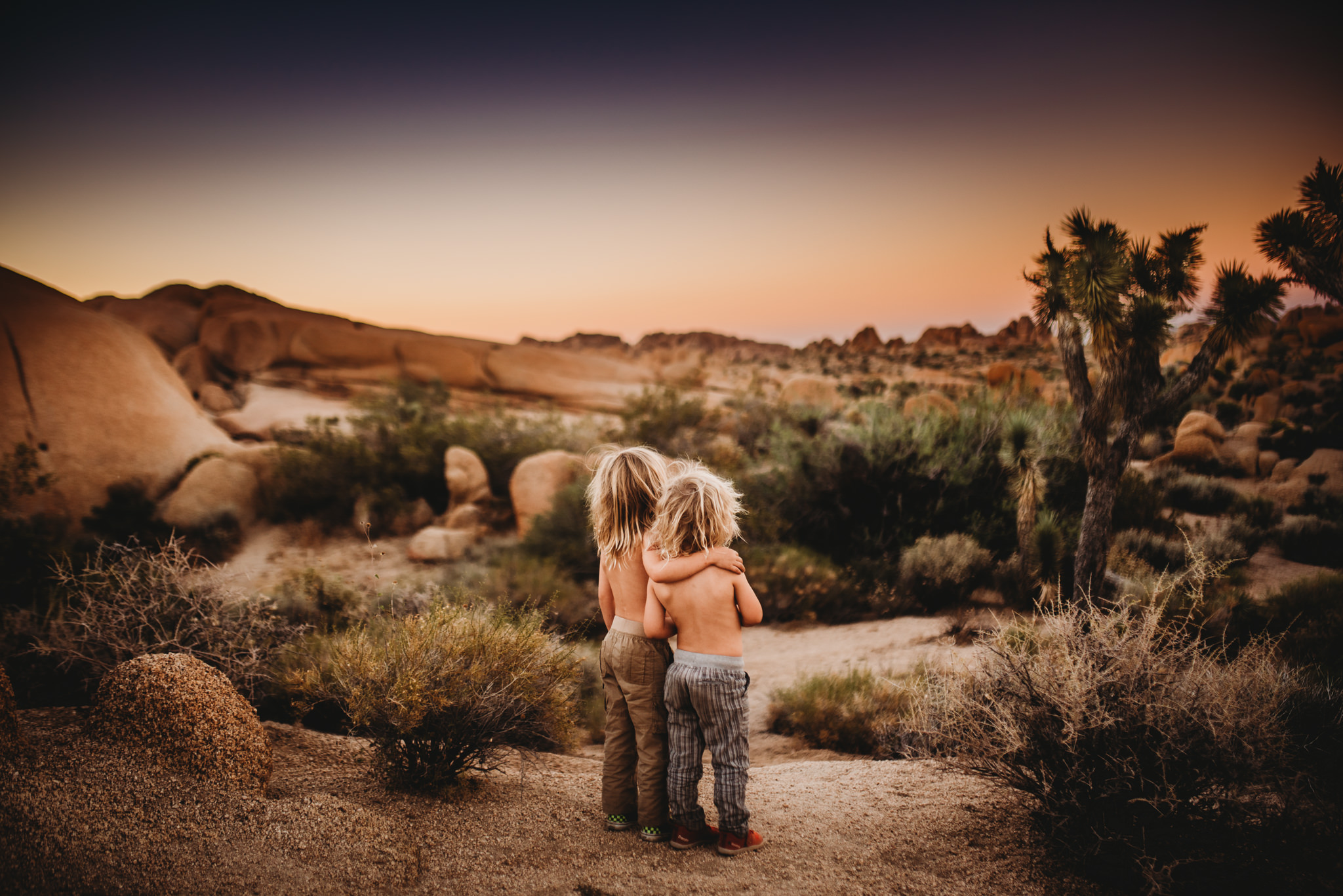 Two children are embracing each other and they are looking towards the moon.