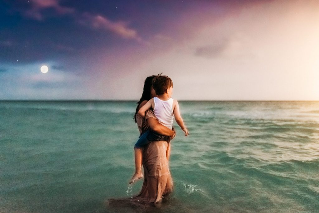 A woman is holding her child and they are standing in the ocean.