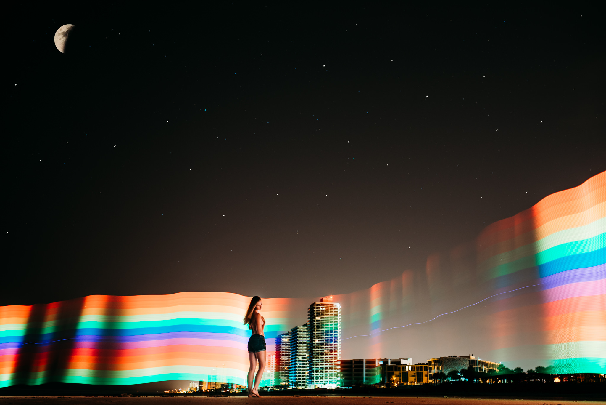 A woman is standing in front of a city with skyscrapers and the Celestial Preset adds a rainbow to the background.