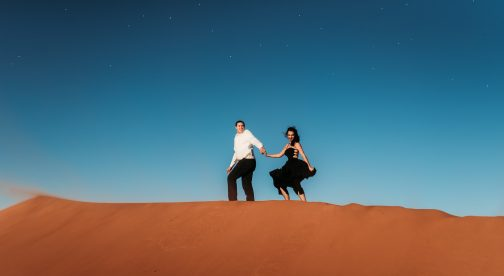 A couple is holding hands and standing on top of a sand dune.