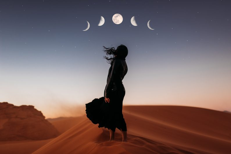 A woman is standing on top of a sand dune.