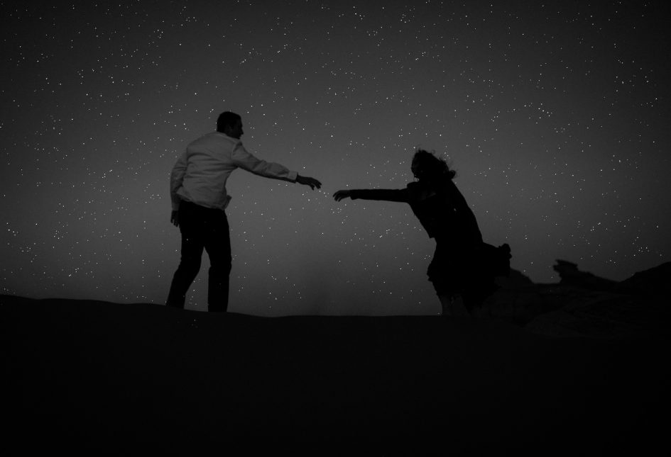 A couple is reaching out to each other and it is nighttime.