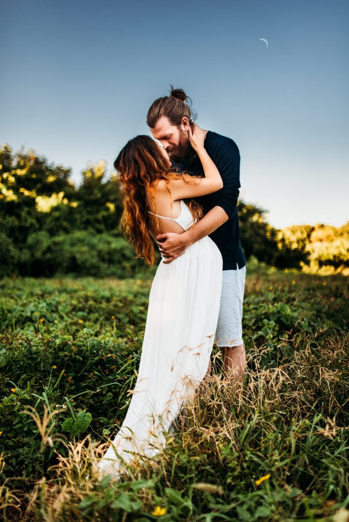 A couple is embracing each other and standing in a meadow.