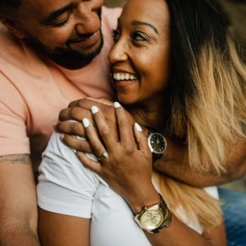 A couple is holding each other and smiling at each other.