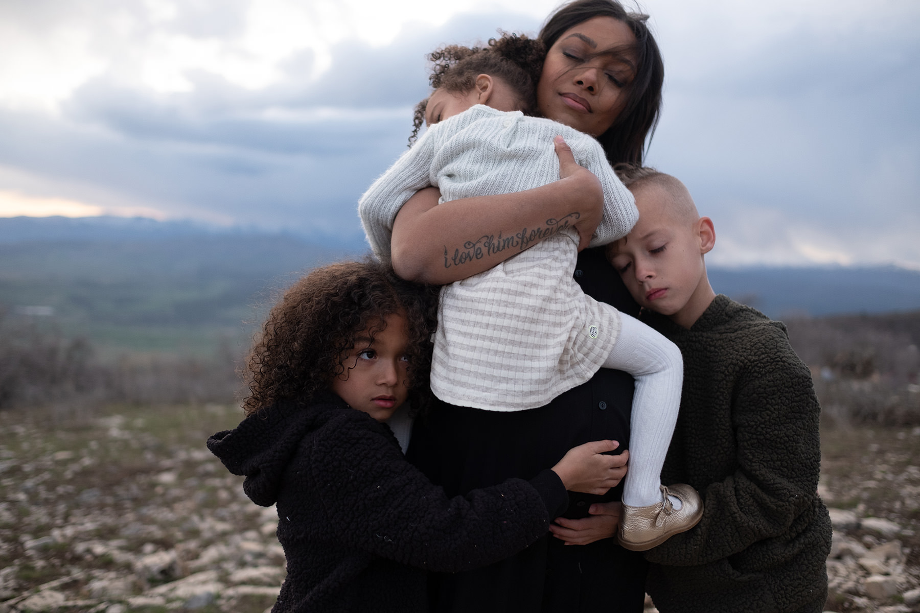 A woman is holding her child and her other two children are hugging her.
