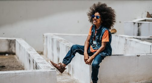A child is sitting on a wall and is smiling.
