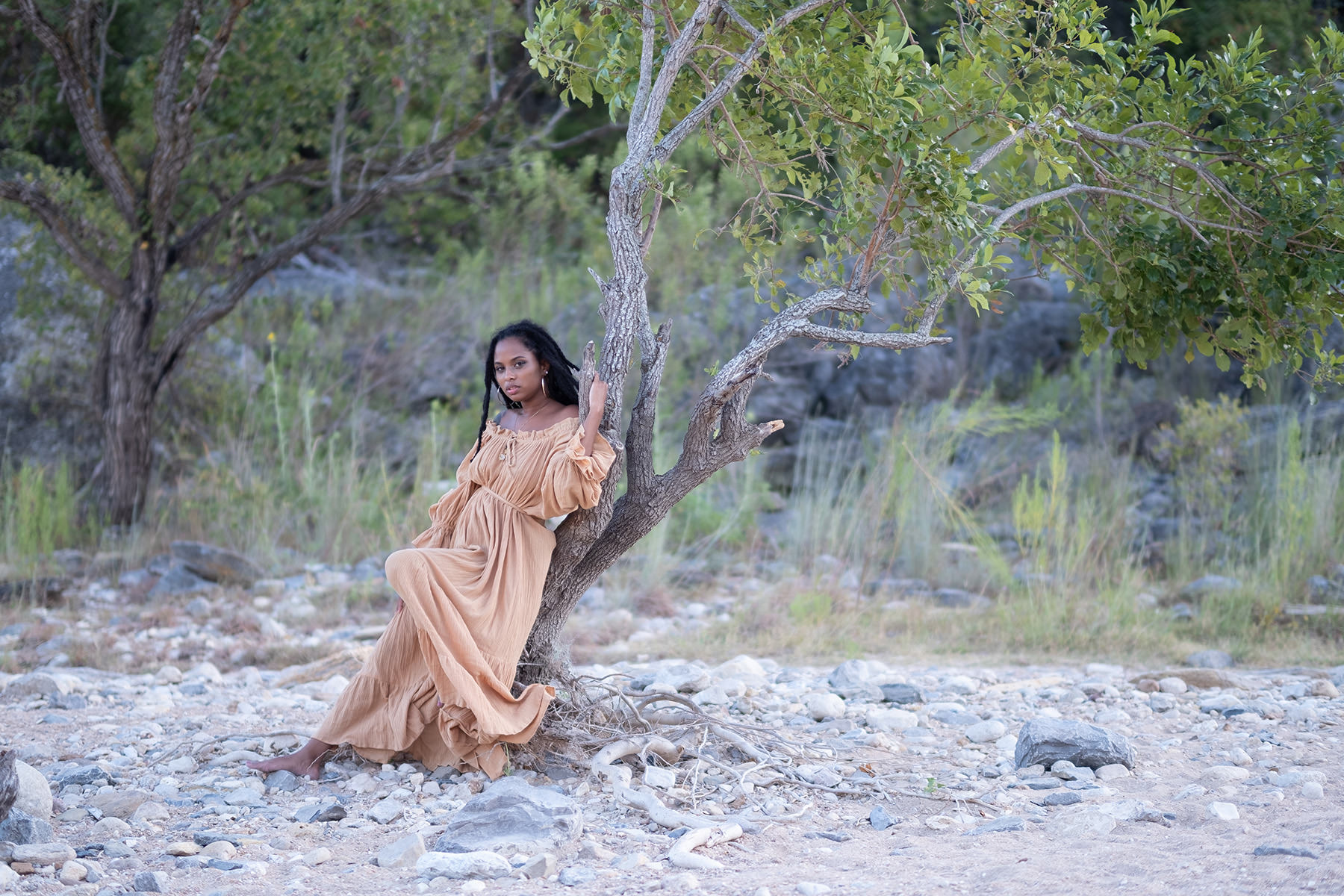 A woman is leaning against a tree.