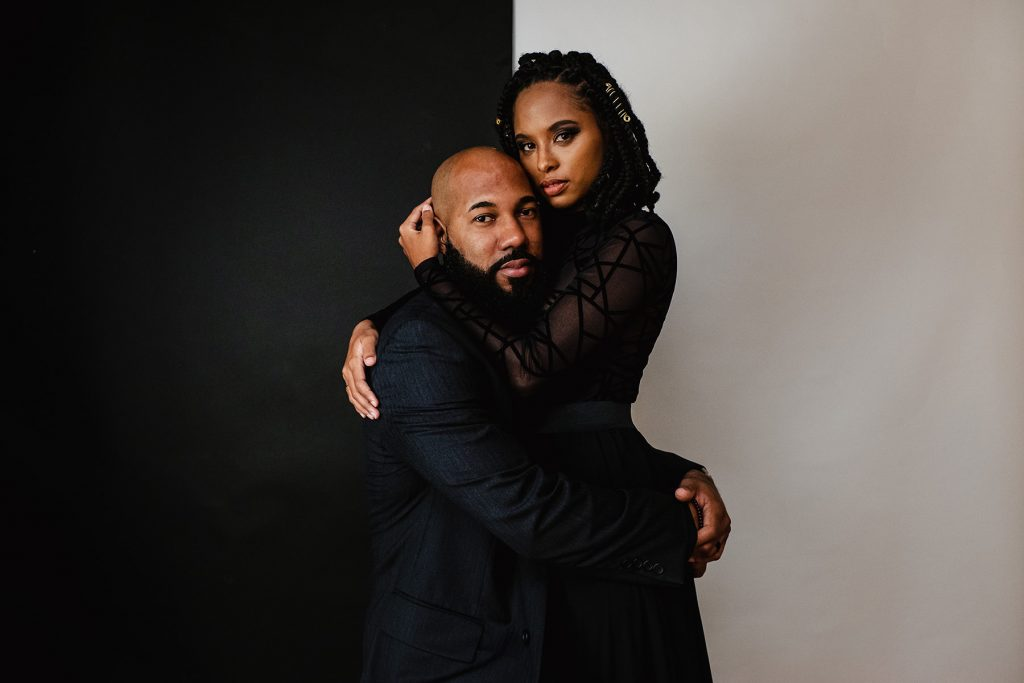 A couple is holding each other and standing in front of a black and white wall.