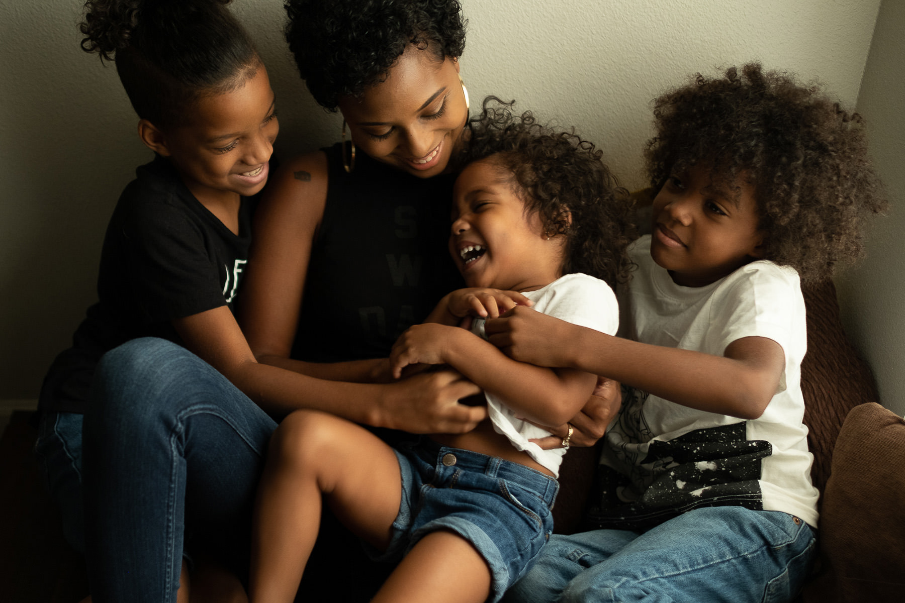 A woman and two of her children are tickling the third one.