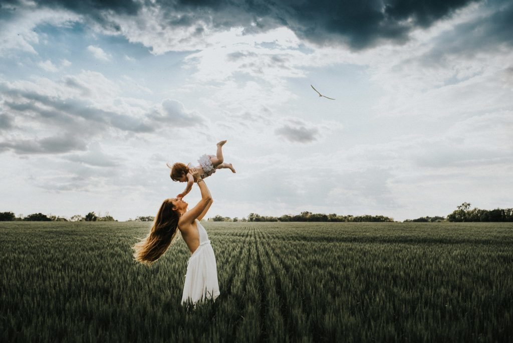 A woman is standing is a field and holding up her toddler.