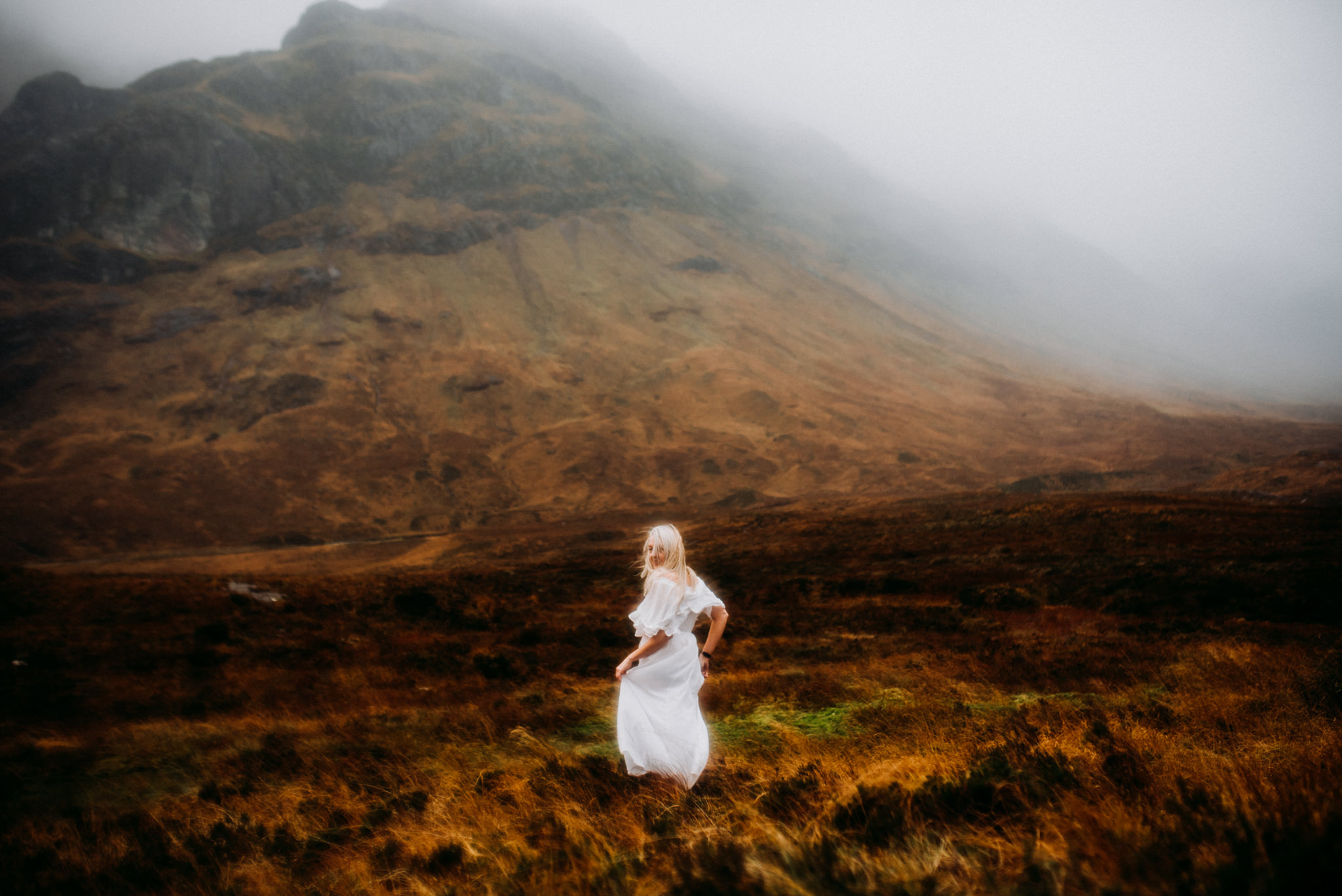A woman is walking through a meadow next to mountains.