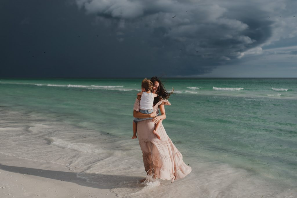 A woman is holding her child and they are standing on the beach next to the ocean.