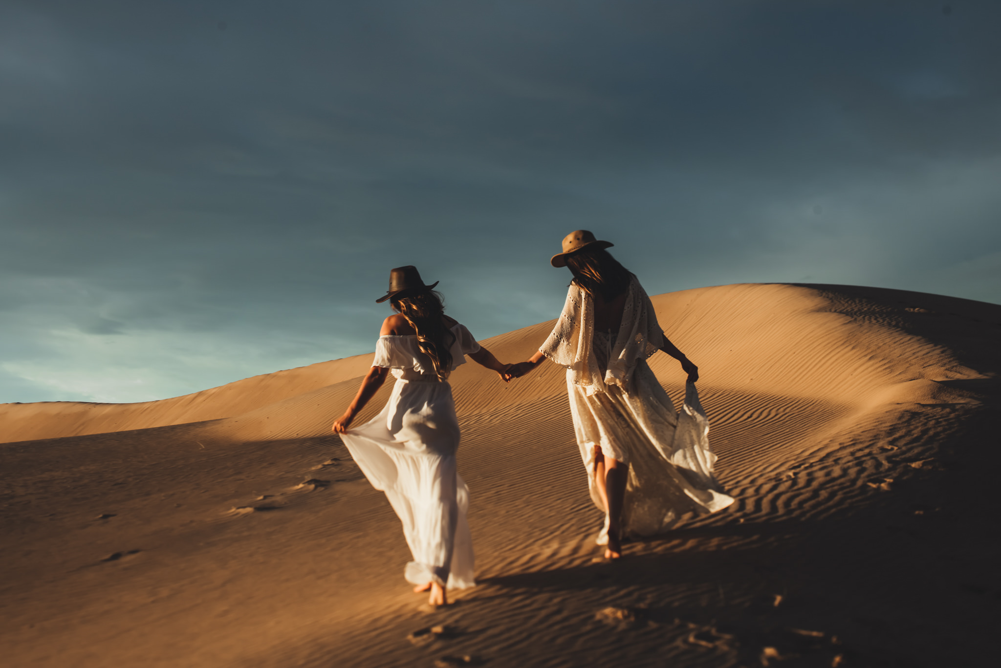 Two woman are holding hands and walking across a sand dune.