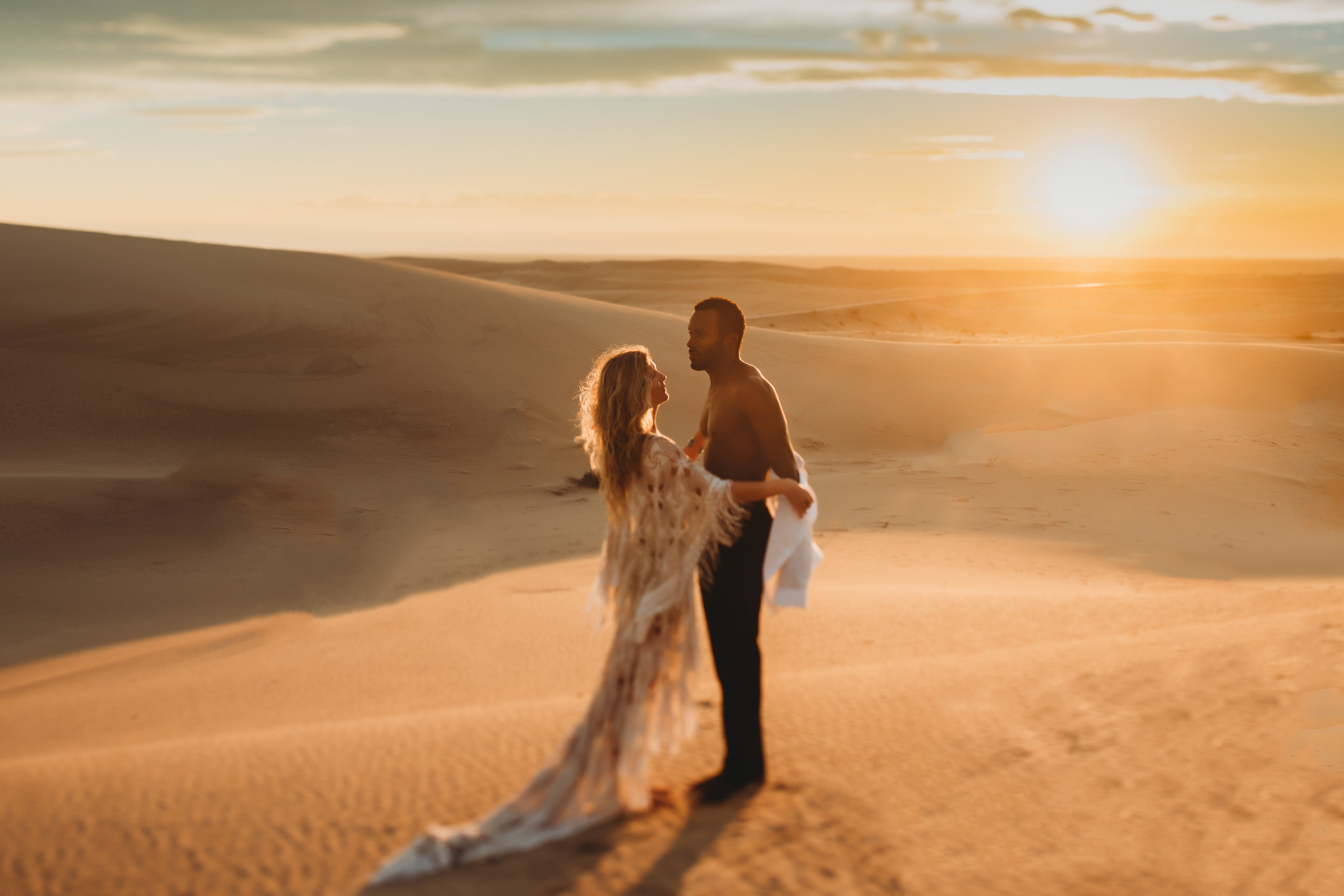 A man and a woman are embracing each other and standing on sand dunes.