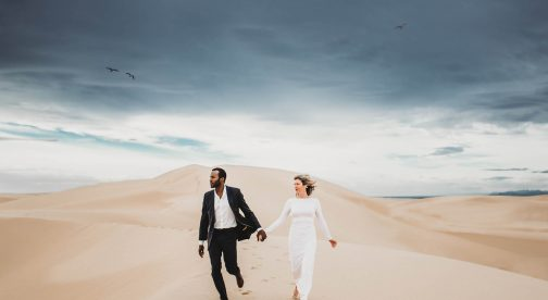 A couple is holding hands and walking on a sand dune.