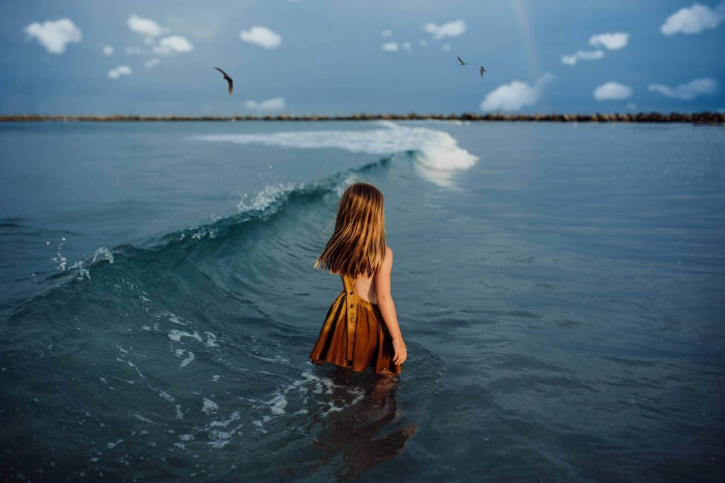 A little girl is standing in the ocean right next to a wave.
