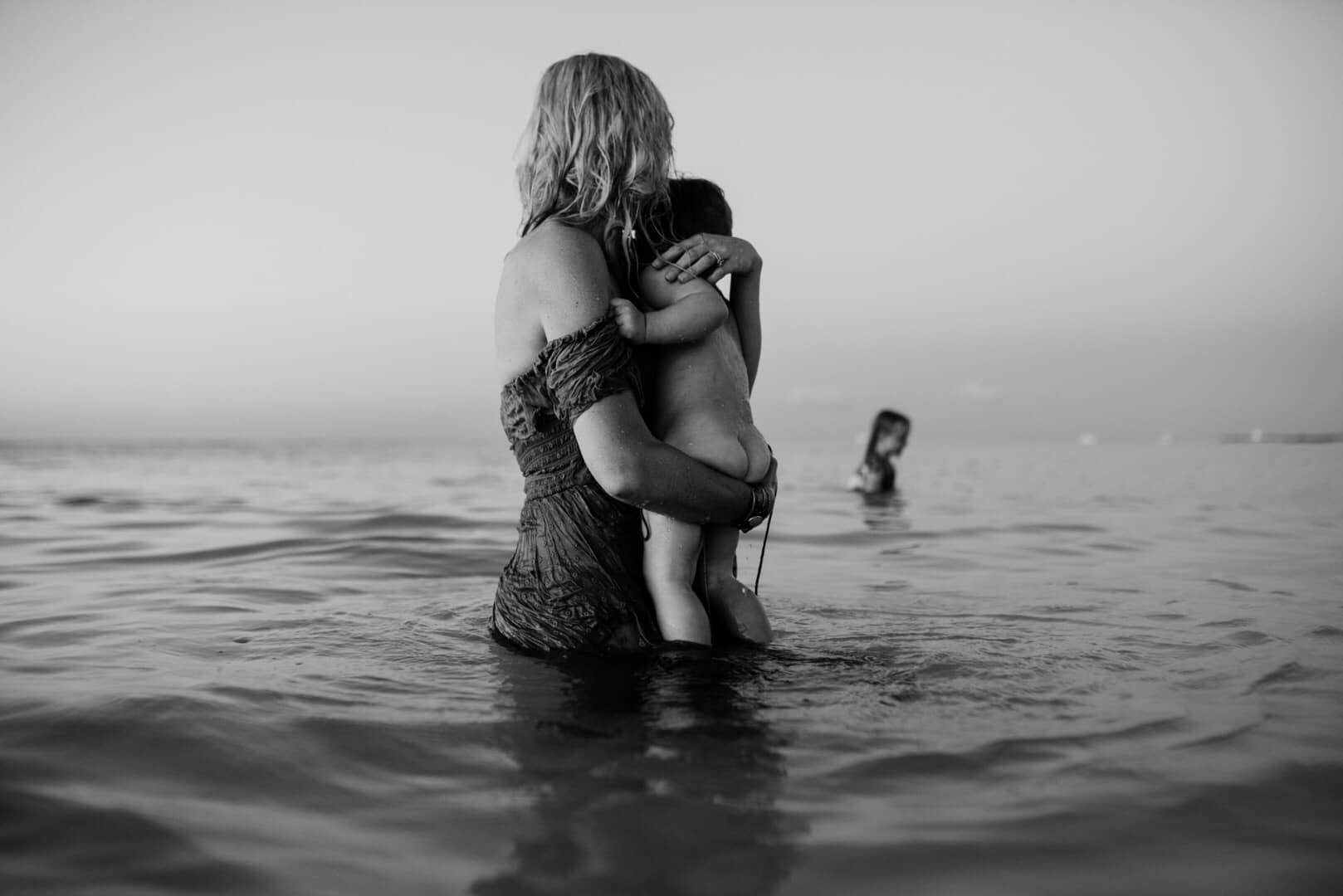 A woman is holding her baby and looking towards another child standing in the ocean.
