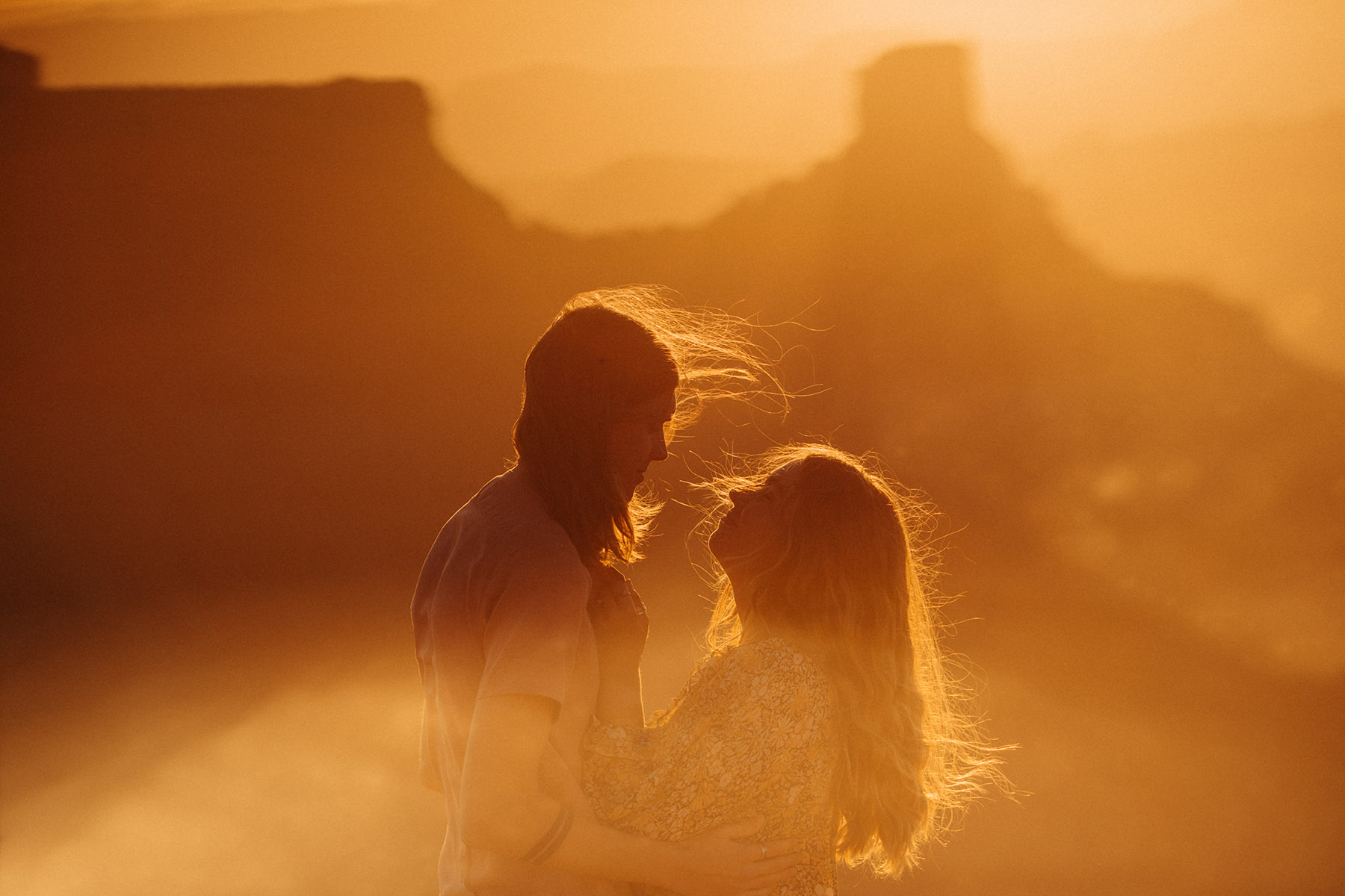 A photo of a couple on top of a canyon with a beautiful sun flare.