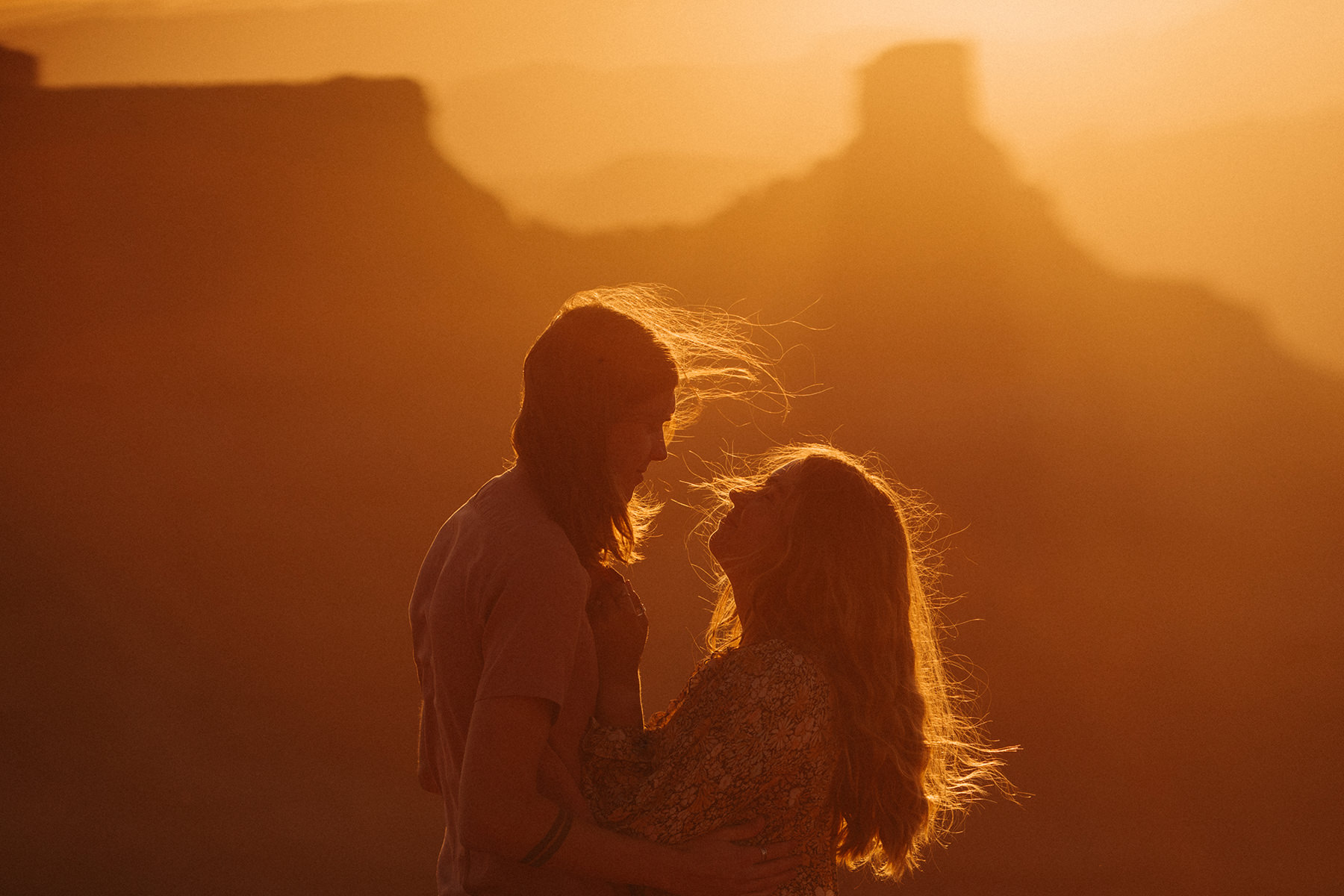 An unedited photo of a couple on top of a canyon.
