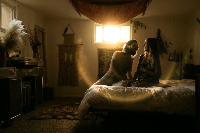 A photo of a couple that sits on a bed and looks at each other while the sun shines through the window.