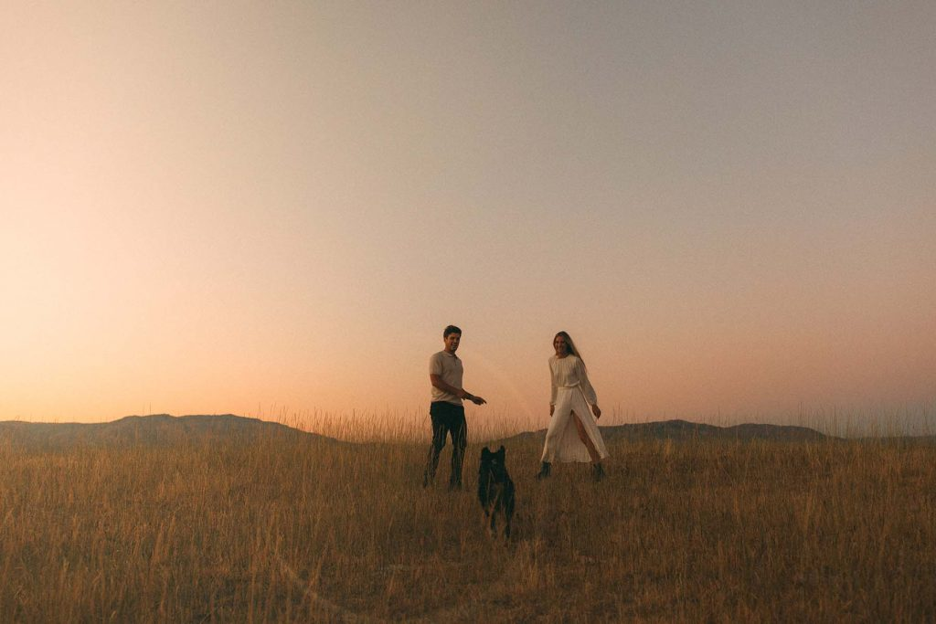 A woman and a man play with their dog on a field during sunset.