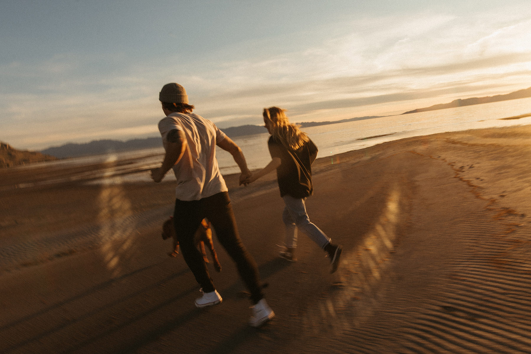 A couple is holding hands and running at the beach.