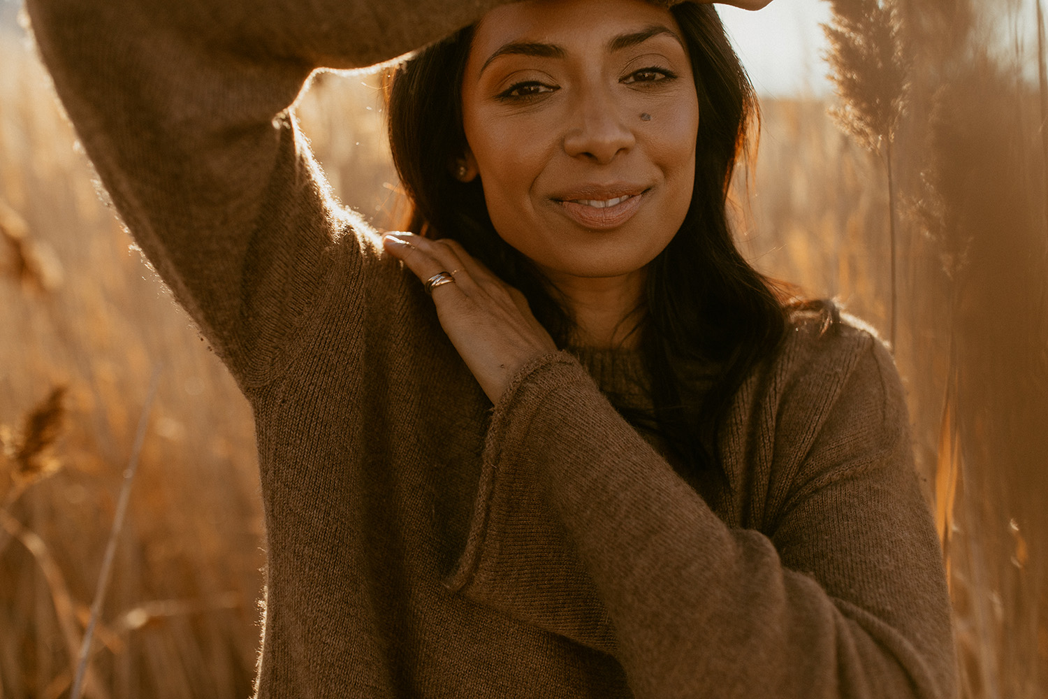 An unedited portrait photo of a woman who stands in a cornfield while the sun shines.